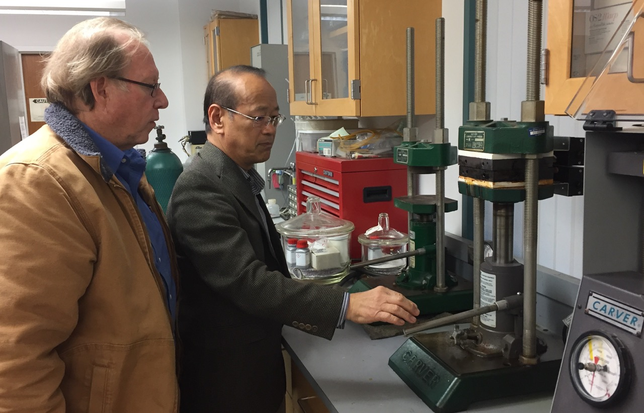 Professor Ishida demonstrates the Carver molding press for film director, John E. Maher