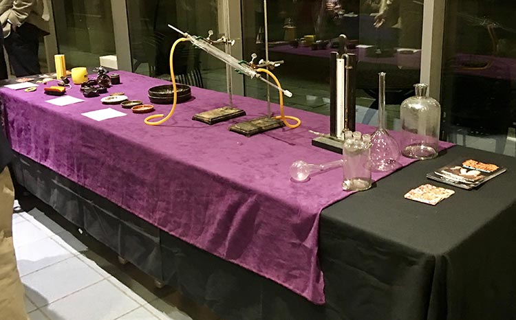A table in the lobby displaying Baekeland laboratory glassware and a manometer. Included are Baekeland family heirlooms and present day Bakelite electrical and automobile parts.